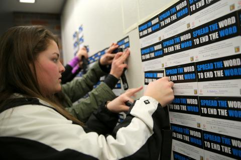 Newtown High School senior Megan Goyda, who is one of the student leaders for the school's Unified Sports program, worked with others on March 24 to post signed pledges in the school's lobby. The pledges will be on view through April 7.  (Bee Photo,…