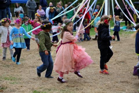 With her classmates, Housatonic Valley Waldorf School kindergartener Izzy Jane Kapsaroff makes her way around the maypole set up for the school's annual May Fair, held on May 9 this year.  (Bee file photo)
