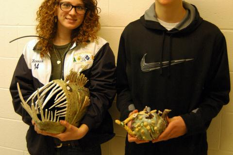 """Hannah Godbout, left, held her """"Angler Fish"""" and Dawson Stout held his """"Sea Tea"""" ceramic pieces on Friday, February 21, before each was shipped off to be part of the Annual National K–12 Ceramic Exhibition."""