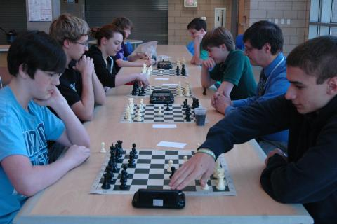 William LeMay, left, and Brendan Gregory faced off in the first round of Newtown High School's Open Chess Tournament, held on Thursday, May 14. Other contenders in the tournament were situated along the table in the school's cafetorium…