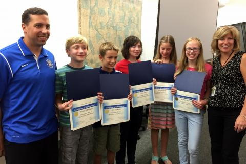 Reed Intermediate School math/science specialist Andrew Hall, left, and Principal Anne Uberti, right, stood with rising sixth grade students, from left, Mitchell Doherty, Justin Peck, Tyler Hill, Jillian Reilly, and Maddie Hintz during a Board of…