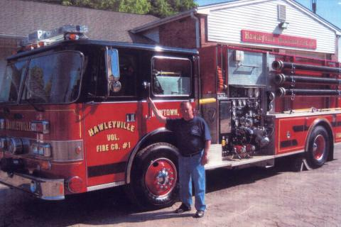 Raymond Fuller, standing next to a Hawleyville Volunteer Fire Company fire truck, has received that organization's Fireman of The Year Award.  (Hawleyville Volunteer Fire Company photo)