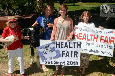 "Holly the calf joins Newtown Health Fair organizers, from left, Mae Schmidle, Judy Blanchard, Della Schmid, and Donna Culbert inviting residents to participate in a ""(Middle) Name That Cow"" contest, as just one of the fun activities that…"