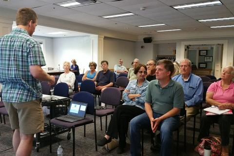 Brian Hartgraves of the Newtown Community Center Advisory Commission, left, opens the final public forum and information session Saturday, June 24, at the Booth Library community room. A number of representatives of other elected and appointed…