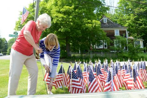 Newtown Woman's Club GFWC members Jan Happel, left, and Chris Duran set flags in place on Friday, May 27, around the Soldiers & Sailors Monument on Main Street. The group has put out the flags annually on Memorial Day weekend since 2009.  (Bee Photo…
