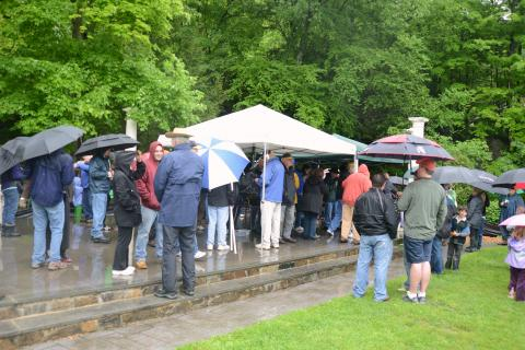 A sea of umbrellas crowds closer to an awning where a raffle for the 13th Annual Great Pootatuck Duck Race winners takes place.