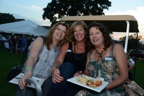 Perched on the back of a golf cart are, from left, Laurie Silber, Amy Edmonds-Casey, and Laura Smolen.