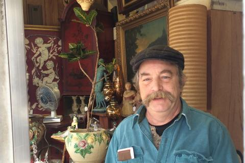 Carl Georgi II, known to most simply as McGeorgi, will be closing his antiques and consignment shop here around the end of February. Standing at the front of his store, he wears his signature tweed ivy cap he is rarely seen without.