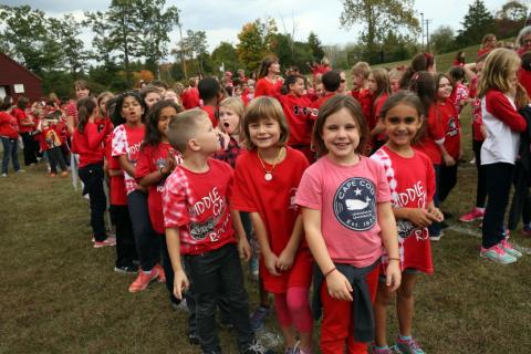 Middle Gate Elementary School students Julia Wologodzeu, front second from left, Mary Guion, front center, and Ashley Jackson, front right, stood together before an aerial photo was taken in October in which the school's student and faculty…