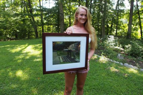 Kateleen Foy, runner-up for inaugural NCAC grant , holds her photograph of a bench at the Public Gardens in Boston.