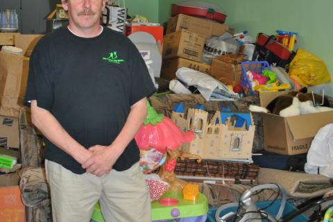 BBBS Donation Center Attendant Mike Thomas stands by a pile of toys and home accessories at the Big Brothers Big Sisters Donation Center on South Main Street, which opened in March.