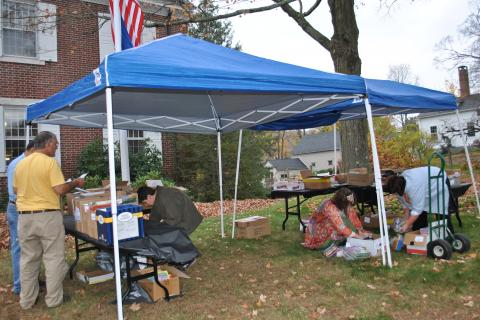"""Monroe residents, who wished to remain anonymous, are assisted by librarian Kim Weber, second from right, as they set up a """"Trick or Read"""" tent in front of C.H. Booth Library on Thursday, October 31."""