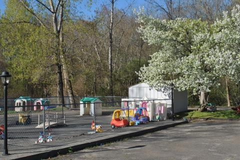 Playgrounds bordered by woods on two sides, behind the main facility, provide children with a peaceful place to explore and have fun, at Misty Morning.