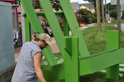 Doug Calderone applies a coat of green paint to a giant Adirondack chair, outside of My Place Restaurant and Pizza, Friday morning, August 29. A lucky winner will take the chair home on Labor Day.