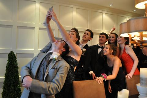 """A number of 2015 NHS Senior Prom attendees huddled together on Friday, April 24, to take a group """"selfie."""""""