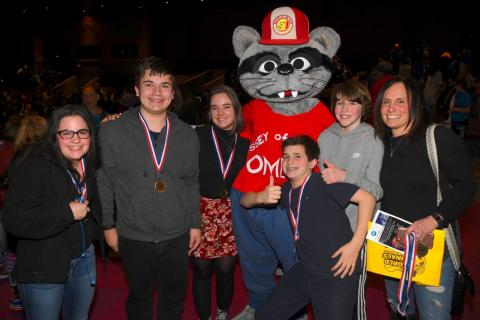 Some of the team members on Odyssey of the Mind Coach Carol Shuman's team stand with her and the program's mascot at the state tournament on March 18. From left are Julia Shuman, Tristan Filiato, Rachel Tramposch, Jacob Shuman, Nick Preszler, and Ms…