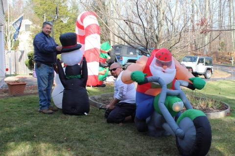 Dave Cicchesi, kneeling, waited for the day after Thanksgiving to set up a display of inflatable Christmas decorations on the front lawn of his Key Rock Road home. While Mr Cicchesi was busy anchoring a penguin playing with a snowman's head,…