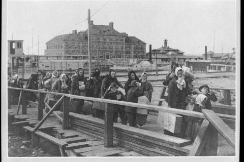Emigrants are seen moving along the boardwalk from a barge, which has taken them off a steamship company's docks, and transported them to Ellis Island, in this photo believed to have been taken circa 1902. Newtown Historical Society will host…