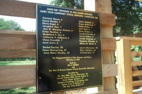 Black Plexiglas signage with laminated faux gold leaf printing lists the names and ages and building information for each Tilt-A-World playground dedicated to the memory of those who were killed on 12/14.