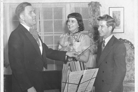Handwritten on the back of this photograph are sparse details about what appears to be a music instructor and students. The information states: Newtown Congregational Church Choir, operetta, April 21, 1950. The woman is holding what appears to be a…