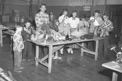 Standing behind a table filled with gourds and vegetables are students of varying ages - one holding a bunny on the right, and another cradling what appears to be a fowl, left. The image is of the Hawley Vo-Ag winners, 1952, according to writing on…