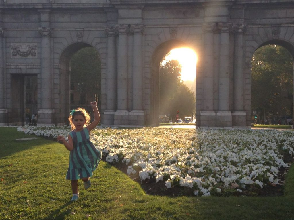 Girl running through Plaza de la Independencia in Madrid