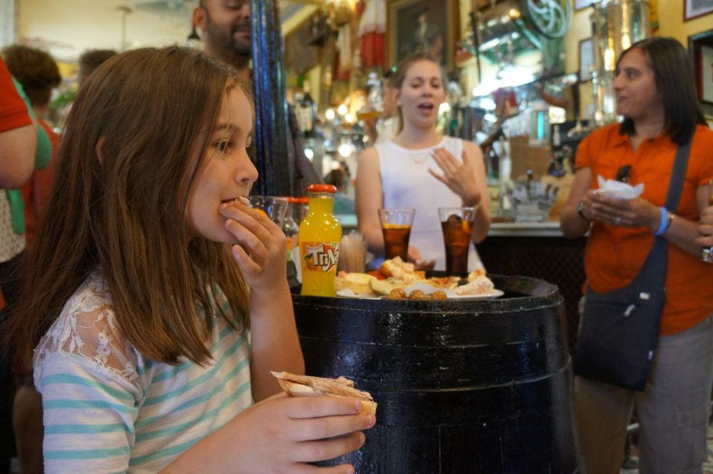 Girl tasting food on food tour in Madrid