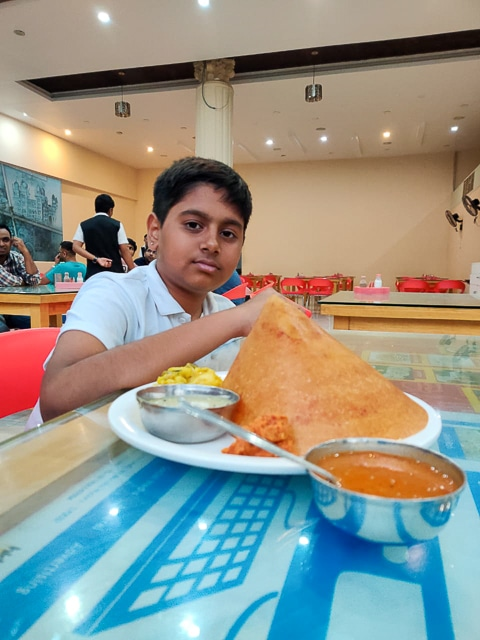 India for kids: boy eating mysore masala dosa