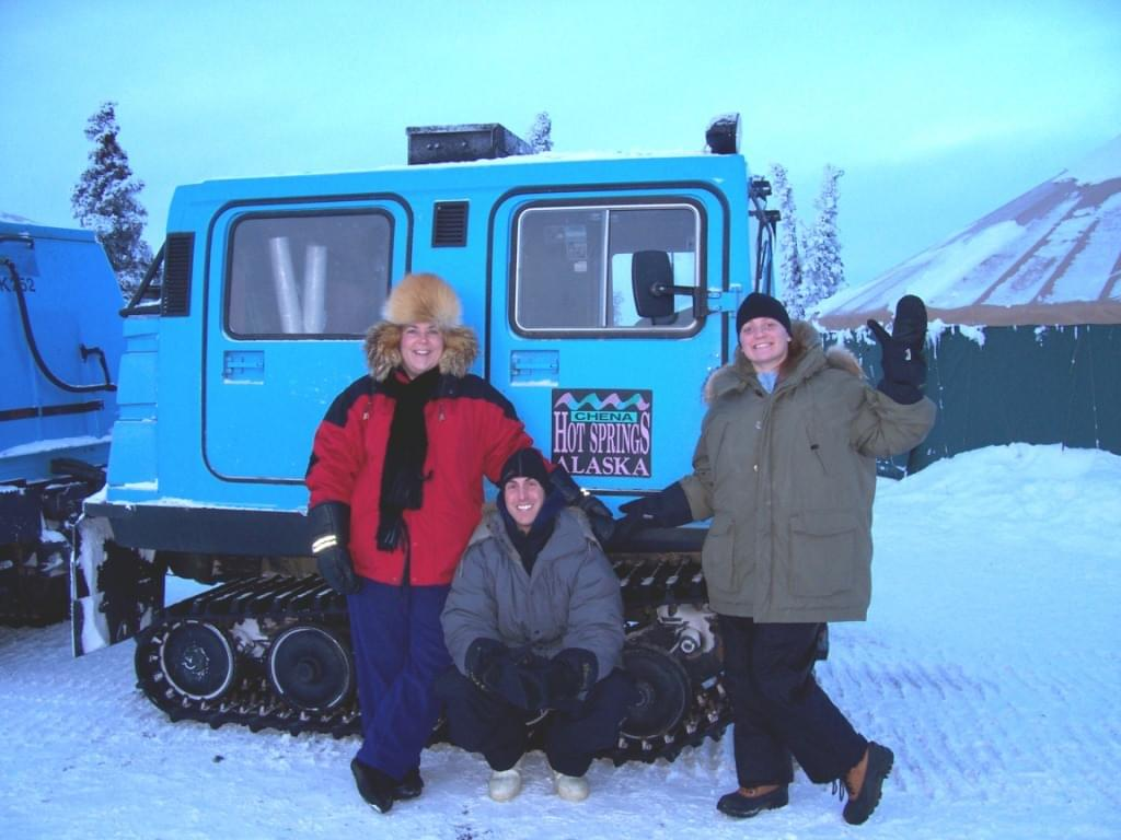 friends in front of a snow coach at chena hot springs in alaska