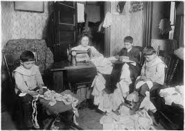 Black-and-white photo showing a family of four sitting in a parlor or living room sewing doll clothes.