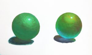 Comparison of two green balls: left ball is straight green, right ball has added interest through additional color in shadows and highlights.