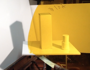 Objects set up to cast a shadow with yellow colored gel sheet