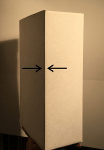 Arrows pointing out high contrast lighting at the corner of a flat-surfaced, rectangular object.