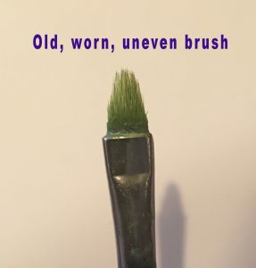 Old, worn paintbrush with uneven bristles.