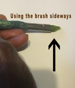 Using the brush sideways when painting grass blades with an old, uneven brush.