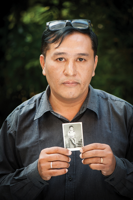 MYANMAR: Lin Thant, a journalist for The Irrawaddy, holds up a photo of himself as a young boy.  The forty-four-year-old journalist spent more than nineteen years in prison. He was arrested while in college when he protested against the Burmese government. Three of his friends were shot and killed during the protest.