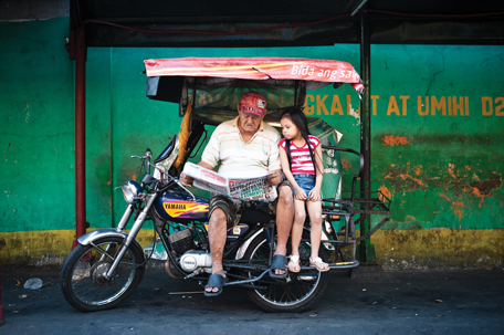 PHILIPPINES: Eighty-three-year-old tricycle driver Demetrio S. Legaspi from Manila reads the paper every day, sometimes with his granddaughter watching. He reads all the newspapers he can get ahold of.
