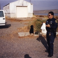 Police officer holding a t-shirt, near Columbia River<br />