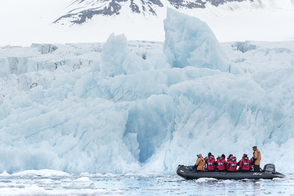 Polar bear viewing on an adventure cruise. Passengers are exploring Spitsbergen by zodiac. Photo: Daisy Gilardini