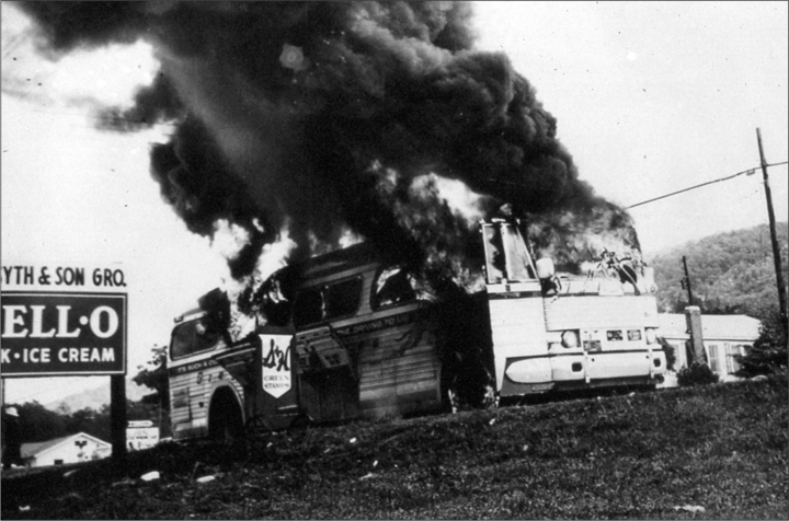 Smoke pours out of the windows and doors of a bus on the side of the road.