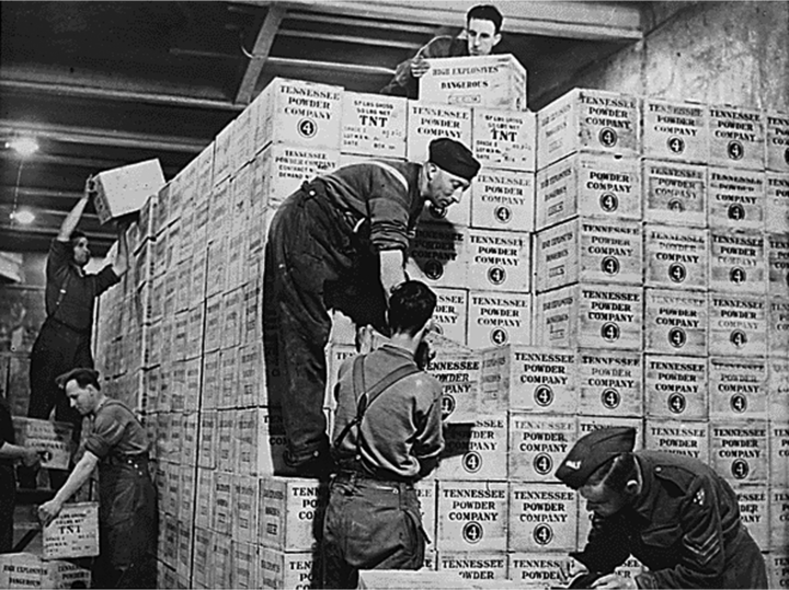Men stack boxes of TNT that reach above their heads. The boxes are labeled