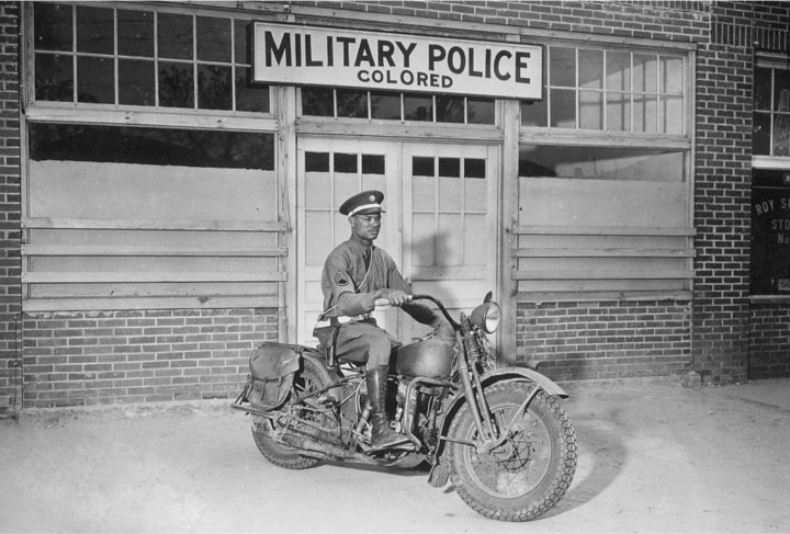 An African American soldier sits on a motorcycle parked in front of the Military Police: Colored building.