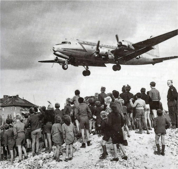 A group of people look up at a low-flying plane.
