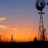 An amazing Oklahoma sunset bathes an old windmill in brilliant hues in western Oklahoma.