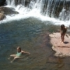 A family enjoys a dip by a waterfall in the adorable getaway village of Medicine Park in southwestern Oklahoma.