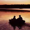 A grandfather takes his granddaughter for a paddleboat ride at sunset on Lake Eufaula.