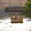 A water taxi captain pilots his boat under a bridge and provides his passengers with a view of a mosaic mural along the canal in the Bricktown Entertainment District in downtown Oklahoma City.