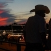 Spectators look on from atop a fence at sunset as the International Finals Youth Rodeo in Shawnee plays out in the background.