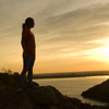 A hiker watches the sun set over Lake Altus-Lugert from a vantage point atop one of the ancient peaks of the Wichita Mountains at Quartz Mountain Nature Park near Lone Wolf.