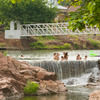 Swimmers enjoy the cool waters of the creek at Medicine Park.  This quaint village features cobblestone cottages, artisans and a historic past as a premier resort town.